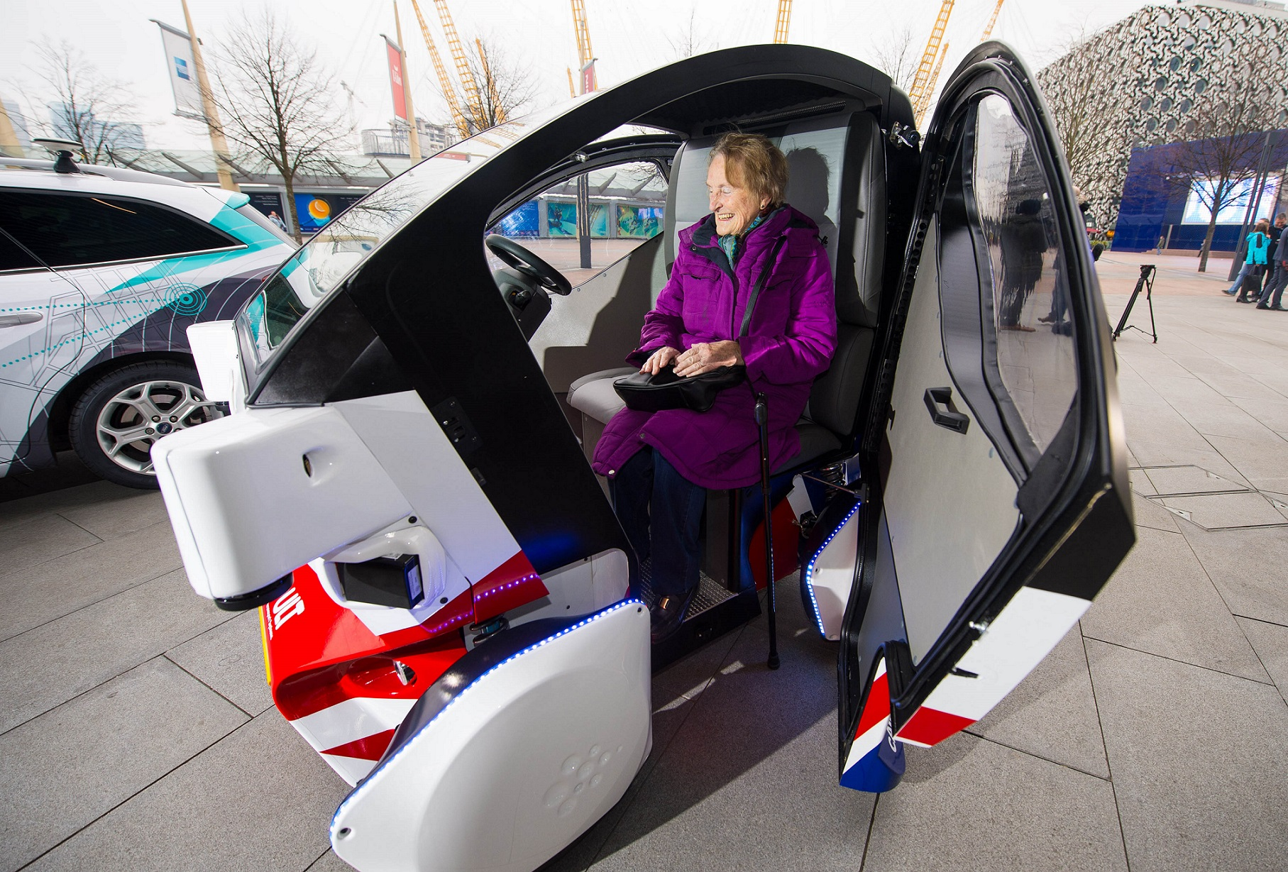 EDITORIAL USE ONLY Brenda Stevenson, 82, from Greenwich sits inside a prototype of the Pathfinder driverless pod, that will be the first autonomous vehicle in the UK to work on public footpaths, which has been unveiled today by the Transport Systems Catapult at a Government launch event in Greenwich, London. PRESS ASSOCIATION Photo. Picture date: Wednesday February 11, 2015. The electric-powered vehicles can seat two people and are designed to work on pavements and pedestrianised areas. They are being built by RDM Group; one of the UKÕs fastest growing advanced engineering companies, and will be equipped with sensor and navigation technology provided by the University of Oxford's Mobile Robotics Group. Photo credit should: Dominic Lipinski/PA Wire