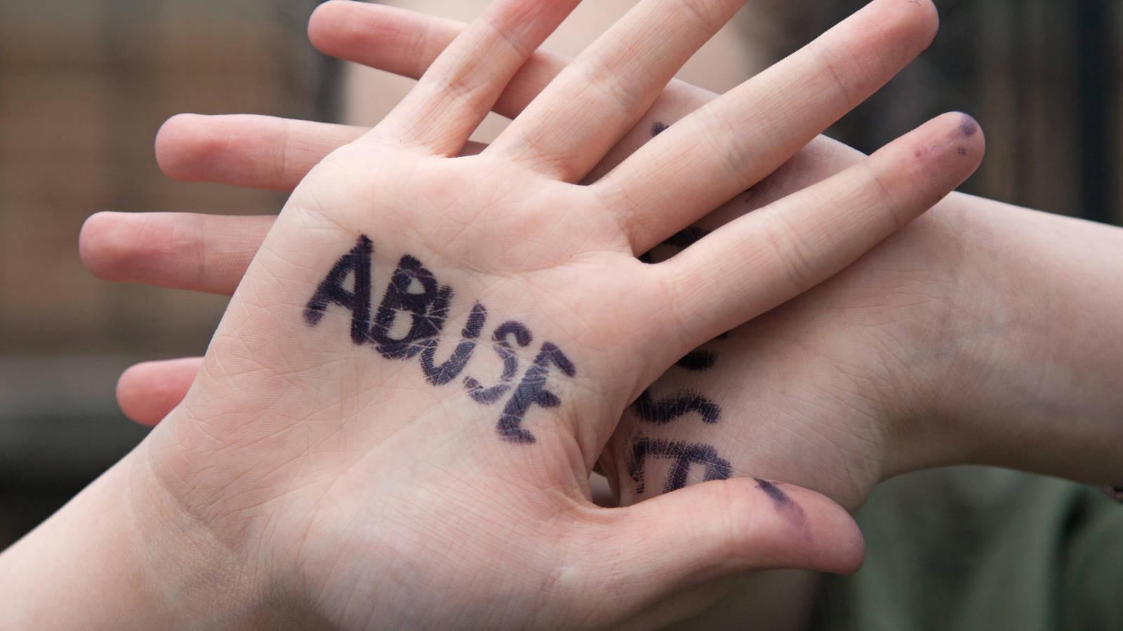 Abuse written on a hand