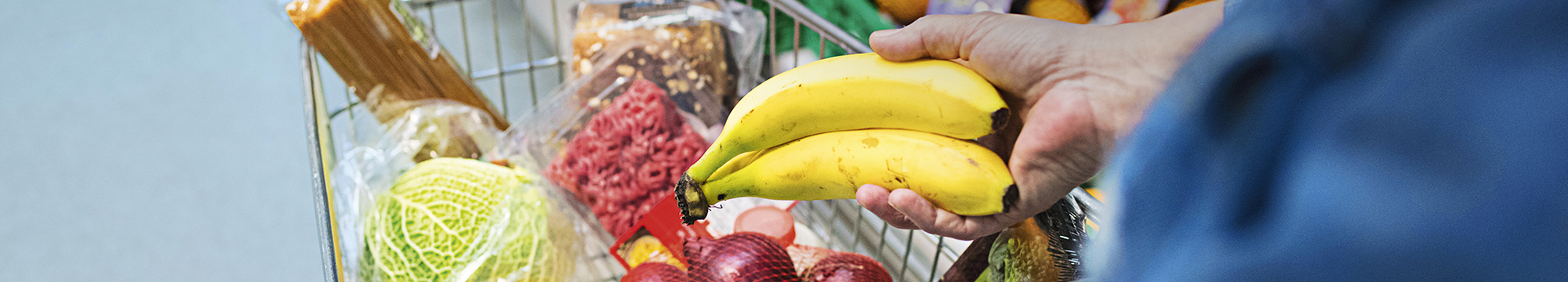 A person putting a bunch of bananas into a shopping trolley at a supermarket