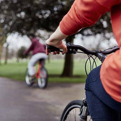 Two people cycling in a park
