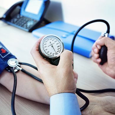 A health professional checking the blood pressure of a patient
