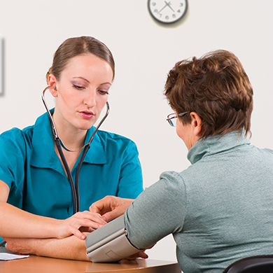 A health professional taking the blood pressure of a patient