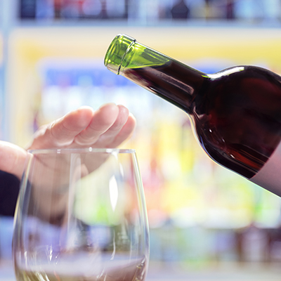 A person's hand rejecting more alcohol from wine bottle in bar