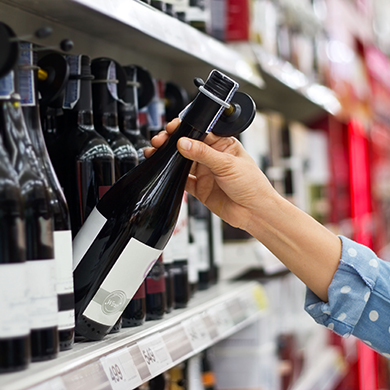 A person taking a bottle of wine off the shelf at a supermarket